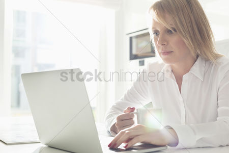 Business : Beautiful mid adult businesswoman using laptop while having coffee at home