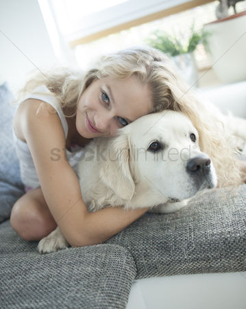 Domesticated animal : Beautiful woman hugging dog on sofa