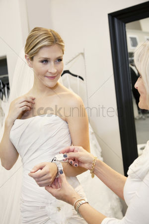 Offspring : Beautiful young bride with mother looking at price tag of bracelet in bridal store