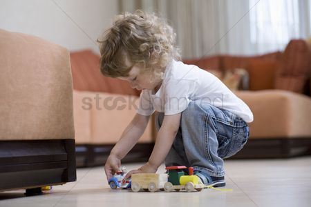 Toy : Blonde toddler playing with toy train on floor