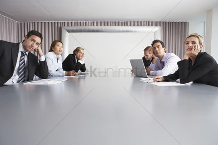 Business Finance : Bored businesspeople sitting in conference room