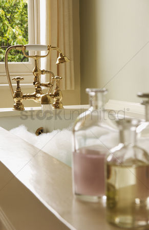 Interior background : Bottles of bath oils on edge of bathtub filled with bubbles water running from tap
