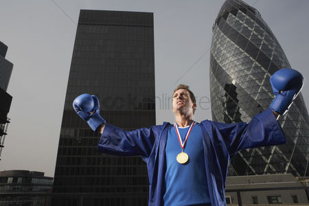 England : Boxer wearing gold medal standing in front of downtown skyscrapers low angle view london england