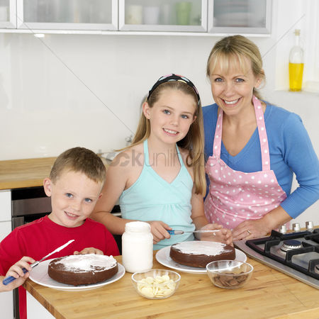 Apron : Boy and girl spreading cream on cake  woman smiling at the camera