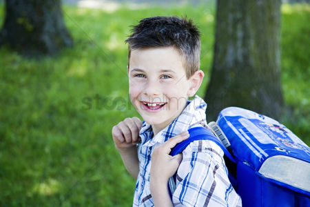 Grass : Boy carrying a school bag on his back