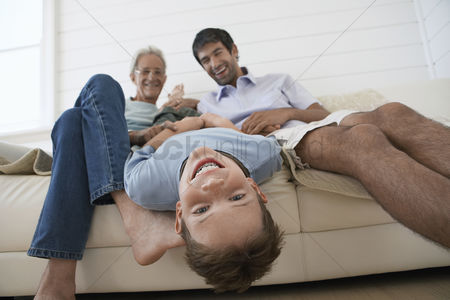 Interior background : Boy hanging upside down off couch with father and grandfather sitting beside him