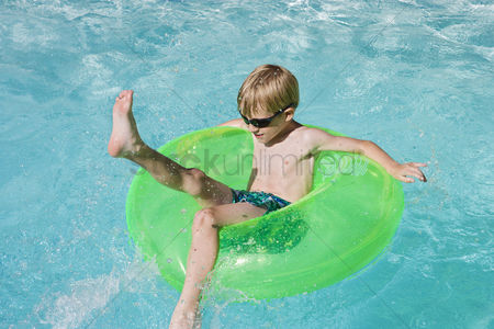 Children playing : Boy on float tube in swimming pool