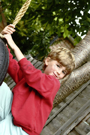 Having fun : Boy playing with a swinging tyre