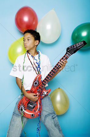 Children playing : Boy playing with an inflatable guitar