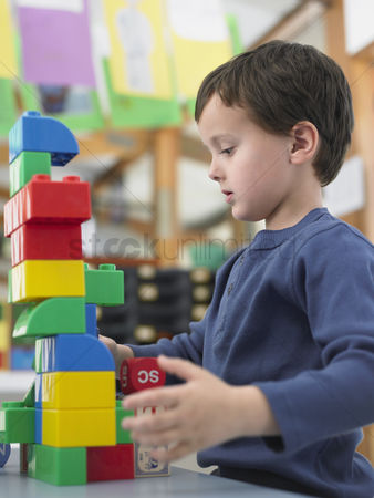 Toy : Boy playing with building blocks in classroom