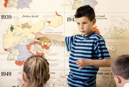School children : Boy pointing at a map while other kids watching