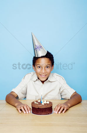 Celebrating : Boy posing with his birthday cake