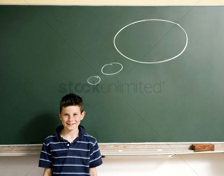 Young boy : Boy standing in front of a blackboard with thought bubble