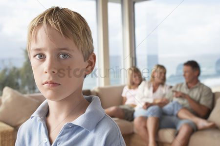 Pensive : Boy standing in room with family in background