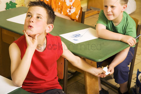 School children : Boys passing note under the table