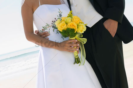 Body : Bride and groom with bouquet on beach  close-up