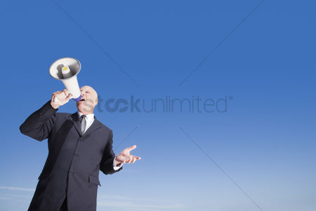 Bald : Busieness man using megaphone standing against sky low angle view