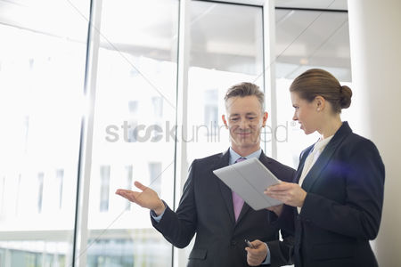 Two people : Business colleagues using digital tablet in office