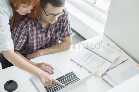 Internet : Business couple using laptop in creative office