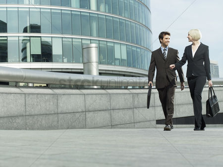 England : Business man and woman walking outside office building talking and smiling