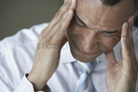 Pain : Business man holding head in hands close up elevated view