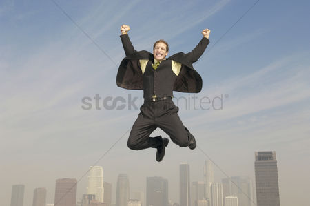 Spirit : Business man pumping fists mid-air above city