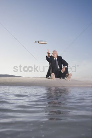 Land : Business man sitting on beach throwing message in bottle into sea low angle view