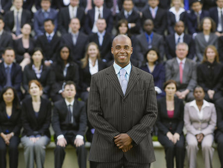 Leadership : Business man standing in front of business people sitting in bleachers portrait