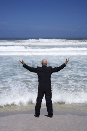 Bald : Business man standing on edge of sea arms outstretched back view
