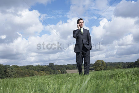 Pocket : Business man talking on mobile phone in field