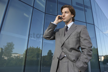 Pocket : Business man using mobile phone outside office building