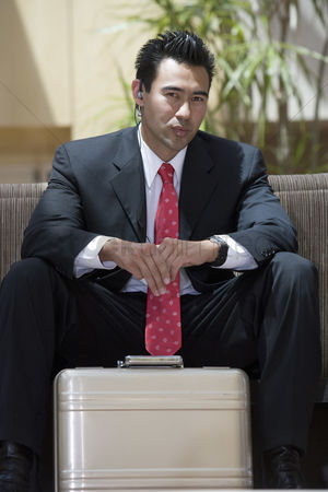 Earpiece : Business man with briefcase indoors portrait