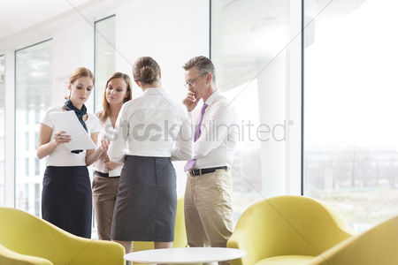 Office worker : Business people discussing over documents in office lobby