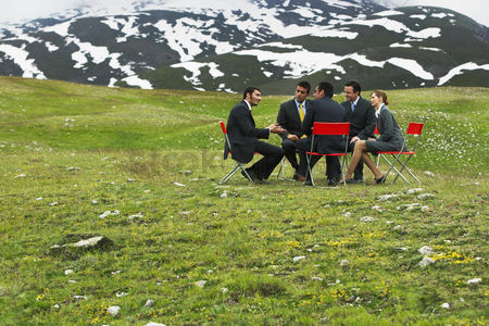Grass : Business people having conference in mountain field