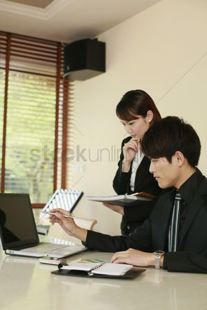 Spending money : Business people having discussion in front of laptop