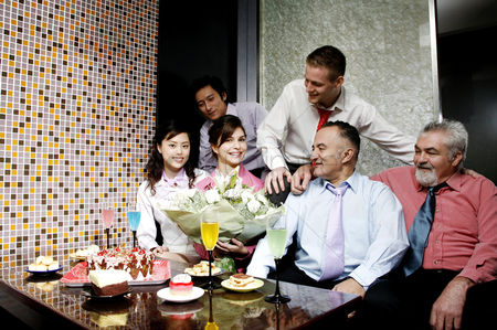 Celebrating : Business people throwing a surprise birthday party for their female colleague