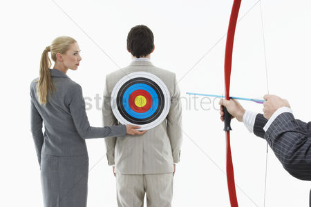 Business suit : Business woman holding target to man s back while other man  close-up of hands  aims bow and arrow against white background