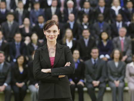Leadership : Business woman standing in front of business people sitting in bleachers portrait