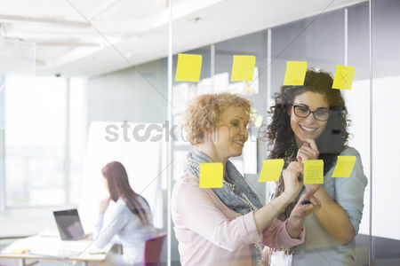 Occupation : Business women brainstorming with sticky notes in office