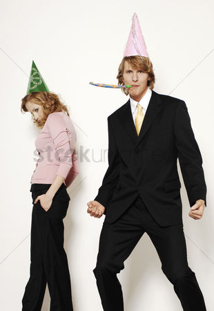 Sullen : Businessman and businesswoman in party hat