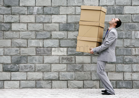 Strong : Businessman carrying a stack of boxes