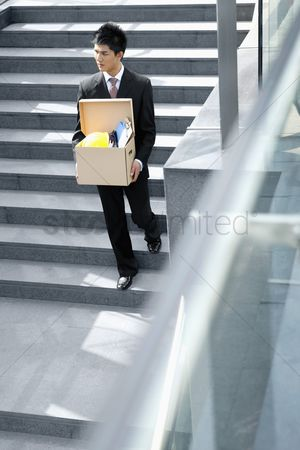 Firing : Businessman carrying box of belongings walking down the stairs