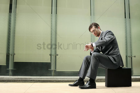 Wondering : Businessman checking the time on his watch while sitting on bag