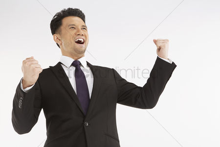 Business suit : Businessman cheering with fists in the air