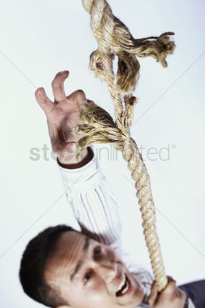 Rope : Businessman climbing a tearing rope