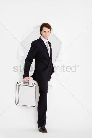 Cardboard cutout : Businessman coming out through a hole torn in paper holding a briefcase