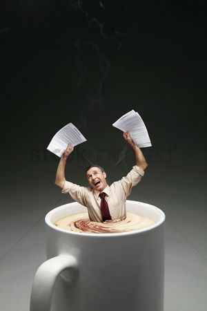 Black background : Businessman drowning in a cup of coffee