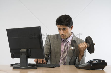 Dumbbell : Businessman exercising with dumbbells and working on a computer