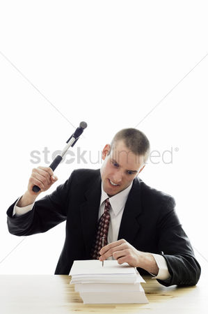Careful : Businessman hammering a nail into a stack of papers