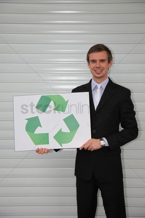 Cardboard cutout : Businessman holding a card with recycling symbol